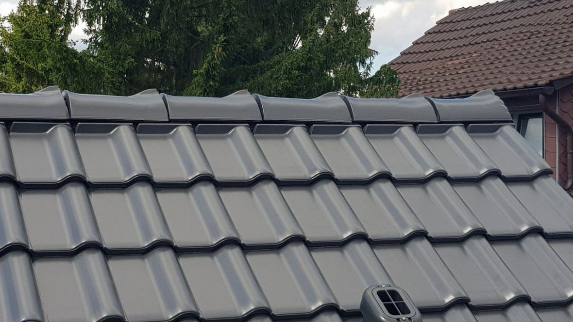 Dachansicht von Mehrfamilienhaus mit Flachdachziegel J11v in lavagrau matt