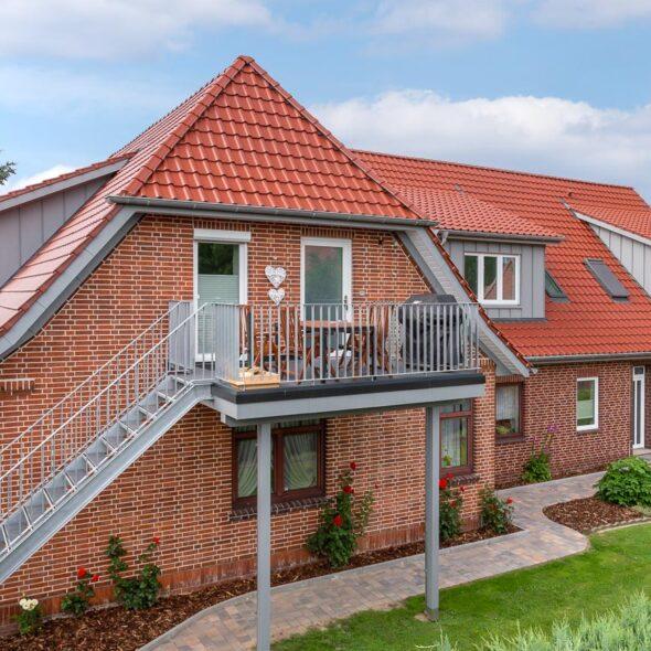 Einfamilienhaus im Landhausstil mit Flachdachziegel J11v in toskanarot matt