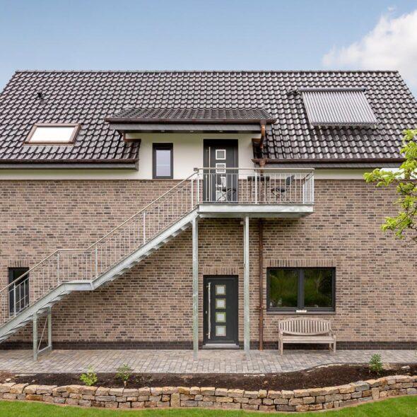 Mehrfamilienhaus mit Flachdachziegel J13v in vulkanscharz matt